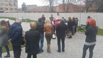 Oameni adunaţi în jurul bustului